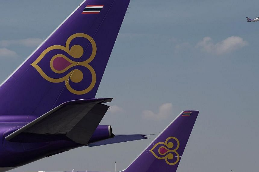 A Thai Airways aircraft takes off past the tails of two other Thai Airways planes at Bangkok's Suvarnabhumi international airport in a November 2014 file photo. Authorities at Lahore airport in Pakistan arrested four men suspected of trying to s
