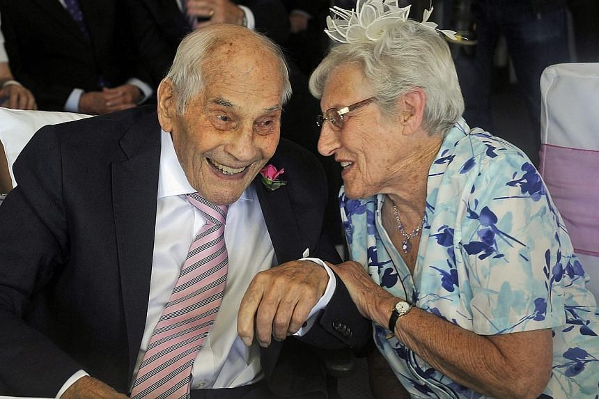 British 103-year-old George Kirby (left) chats with his newly married wife, 91-year-old Doreen Luckie (right), during their wedding party at the Langham Hotel, Eastbourne, East Sussex, Britain on June 13, 2015. -- PHOTO: EPA