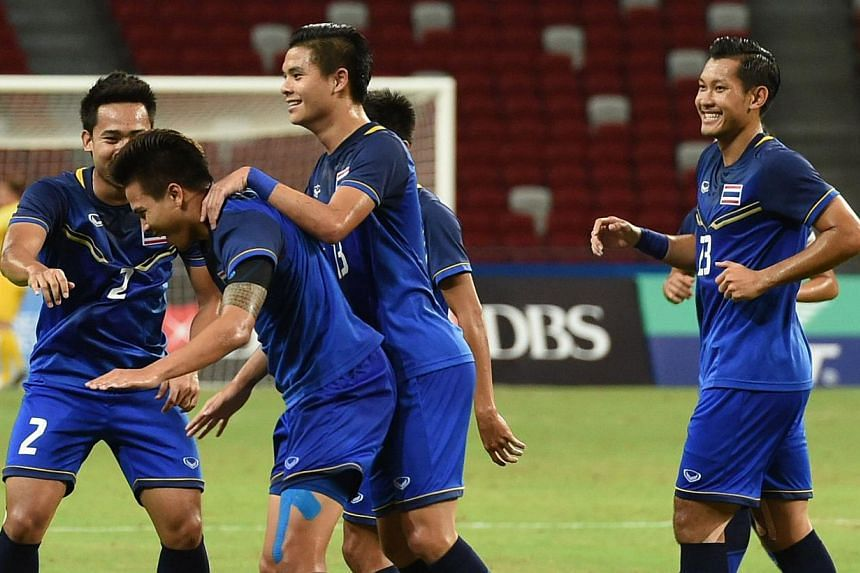 Thailand Thitiphan Puangjan (second left) celebrating with his teammates after scoring his team's second goal during SEA Games football semi-final against Indonesia. -- PHOTO: AFP