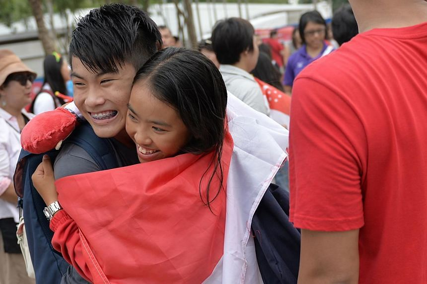 Jodie Lai receives a hug from her brother Thaddeus after she won the gold medal in the female single handed optimist (U16) finals.-- ST PHOTO:CAROLINE CHIA