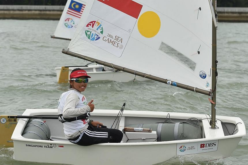 Singapore's Jodie Lai gives a thumbs up to the media after coming in first in the female single handed optimist (U16) finals on June 13, 2015.-- ST PHOTO:CAROLINE CHIA