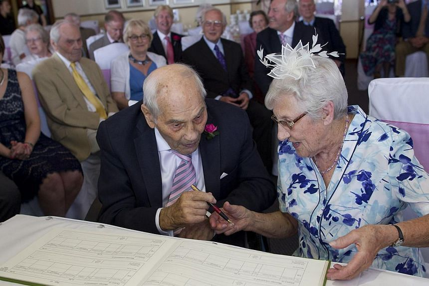 Doreen and George sign the register during their wedding ceremony at the Langham Hotel in Eastbourne, southern England on June 13, 2015. -- PHOTO: AFP