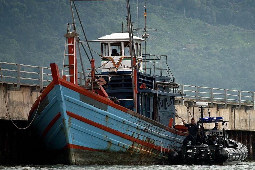 Malaysian maritime police inspecting a boat which carried illegal migrants in Langkawi on May 12, 2015. -- PHOTO: AFP