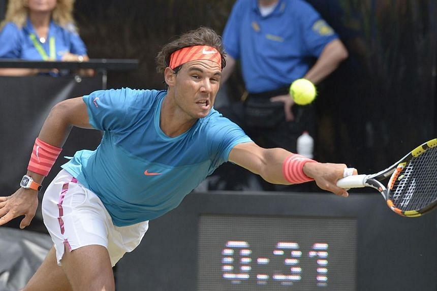Spain's Rafael Nadal returns the ball to Australia's Bernard Tomic during their quarterfinal match at the ATP Mercedes Cup tennis tournament in Stuttgart, southern Germany, on June 12, 2015. -- PHOTO: AFP