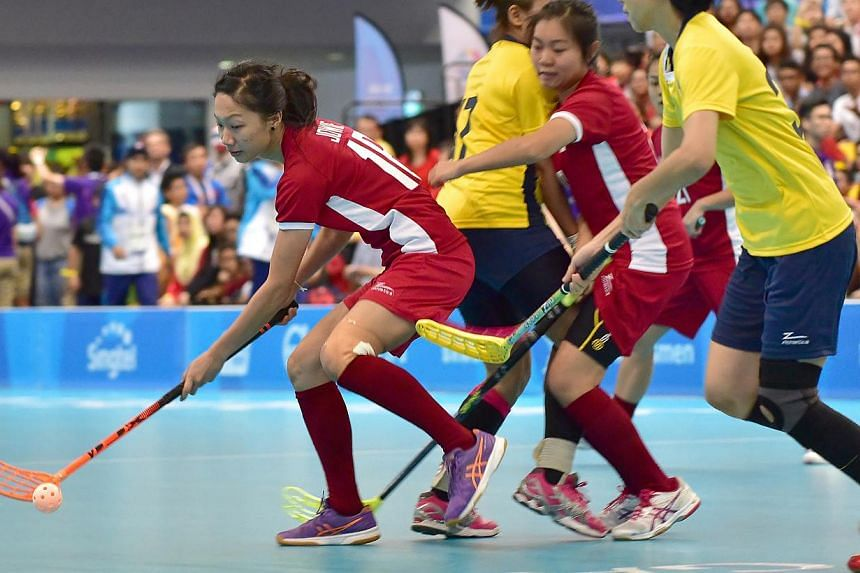 Singapore's Natalia Claire Wee Tuning (right) in action with Malaysia's Cheah Pei Yi in a Preliminary round Floorball match. -- PHOTO: SINGAPORE SEA GAMES ORGANISING COMMITTEE/ACTION IMAGES VIA REUTERS