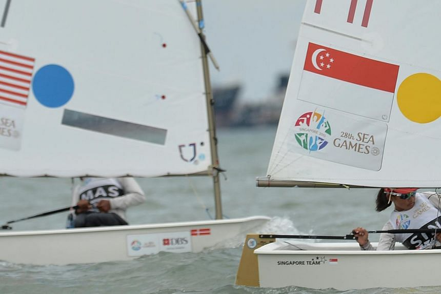 Singapore's Jodie Lai (right) competes in the female single handed optimist (U16) finals on 13 June 2015. She won the gold medal. -- ST PHOTO: CAROLINE CHIA
