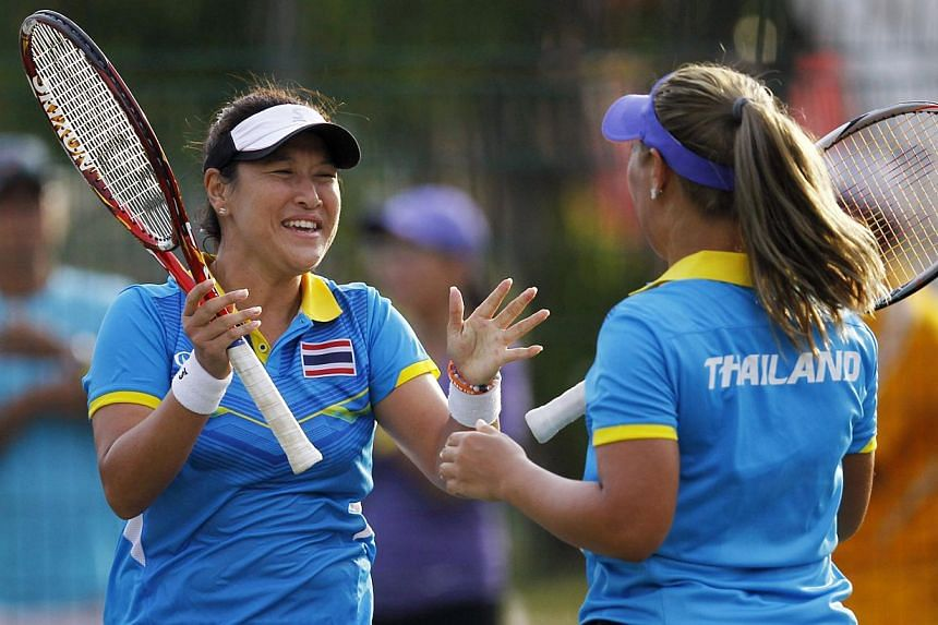 Thailand's Tamarine Tanasugarn and Noppawan Lertcheewakarn celebrate as they win the gold medal in the Tennis Women's Team Final. -- PHOTO: SINGAPORE SEA GAMES ORGANISING COMMITTEE/ACTION IMAGES VIA REUTERS