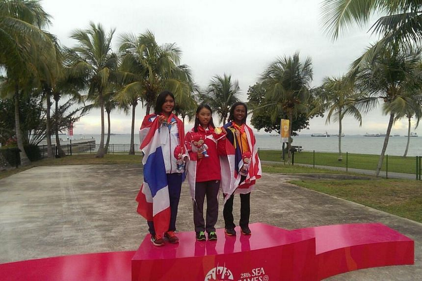 Singapore sailor Jodie Lai (centre), 14, on the podium after winning the female optimist (U16) event on June 13, 2015. Thailand's Kamonchanok Klahan (left) took the silver while Malaysia's Nazri Nabila Natasha settled for bronze. -- ST PHOTO: TOH TIN