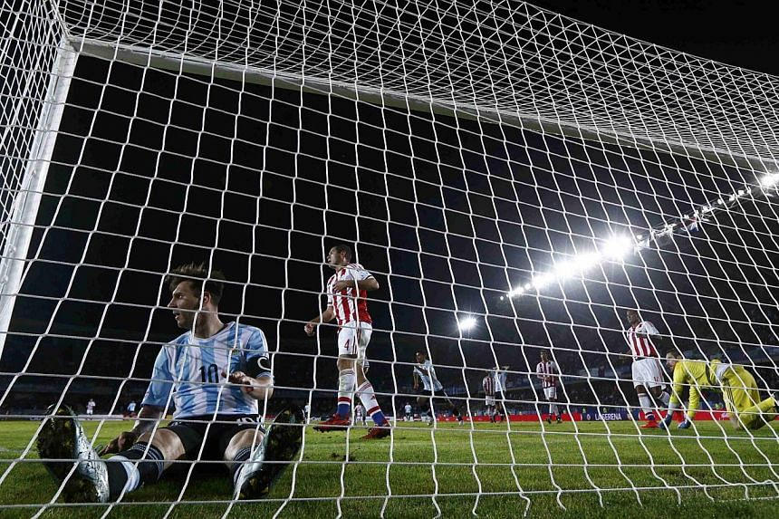Argentina's Lionel Messi (left) sits in the net after missing a goal against Paraguay during their first round Copa America 2015 football match at Estadio La Portada de La Serena in La Serena, Chile, on June 14, 2015. -- PHOTO: REUTERS
