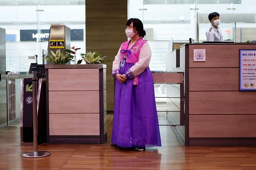 An employee dressed in a Hanbok traditional costume wears a mask to prevent contracting Middle East Respiratory Syndrome (Mers) as she stands in front of a check-in counter at the Incheon International Airport in Incheon, South Korea on June 14, 2015