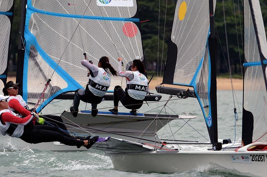 Gold medalists for the skiff49erfx event, Griselda Khng and Sara Li of Singapore (in red) with Malaysia's Rufina Tan and Connie Tsen during the race.-- ST PHOTO:DESMOND FOO