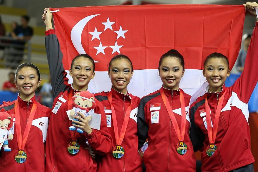 The Singapore rhythmic gymnastic quintet of Dawne Chua, Noelle Goh, Ann Sim, Edlyn Ho and Alison Tang posing with their gold medals after winning the group all-around event. -- PHOTO: SINGAPORE SEA GAMES ORGANISING COMMITTEE/ACTION IMAGES VIA REUTERS