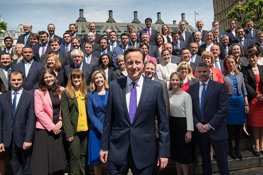 British Prime Minister David Cameron (centre) poses for a group photo with newly-elected Conservative MPs at the Houses of Parliament in central London on May 11, 2015. -- PHOTO: AFP
