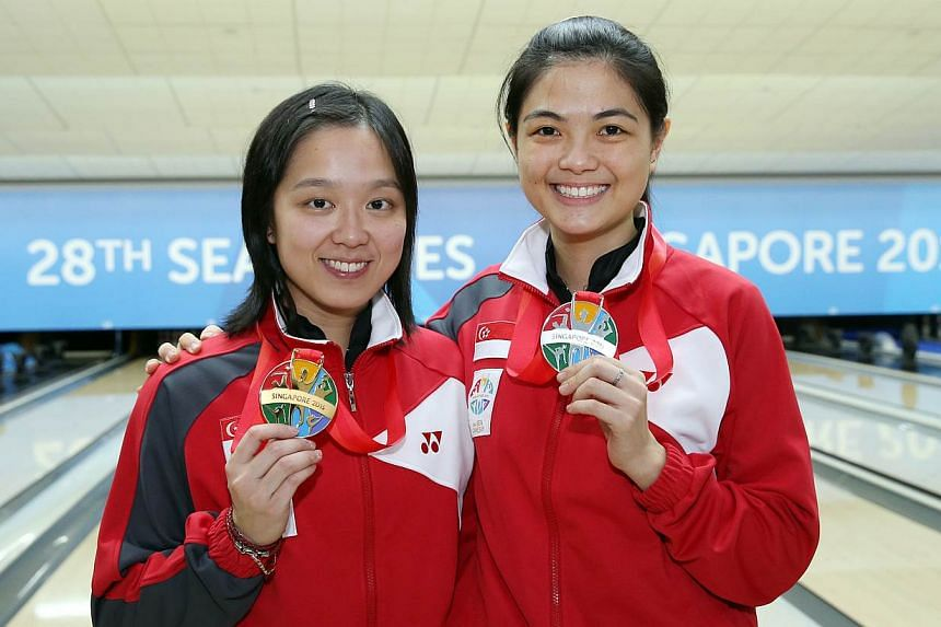 (Left-right) Singapore's Jazreel Tan and Daphne Tan finishing first and second respectively in the bowling women's masters final of the 28th SEA Games on Sunday, on June 14, 2015, at the Orchid Country Club. -- ST PHOTO: SEAH KWANG PENG