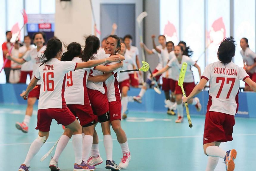 The Singapore women's floorball team celebrating during their match against Thailand. Singapore won the game 2-1 on penalties after the match ended 3-3. -- ST PHOTO: ONG WEE JIN