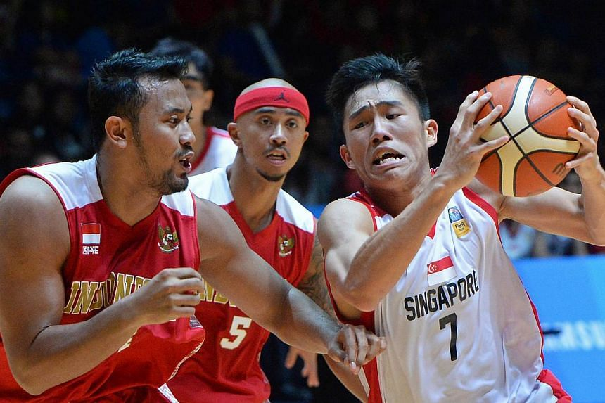Singapore's Wu Qingde (right) attempting to fend off Indonesia's Adhipratama Putra in their men's basketball semi-final at the OCBC Arena on June 14, 2015. -- ST PHOTO: CHONG JUN LIANG