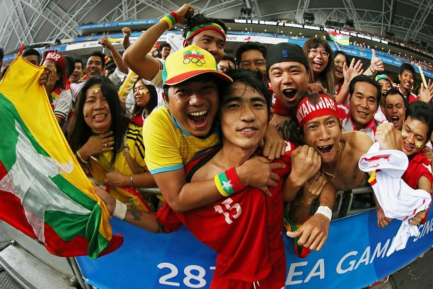 Myanmar footballer Zaw Hein Thiha (centre) celebrating with fans after his country's shock 2-1 win over Vietnam in the SEA Games men's football semi-finals at the National Stadium on June 13, 2015. -- PHOTO: SINGAPORE SEA GAMES ORGANISING COMMITTEE/A