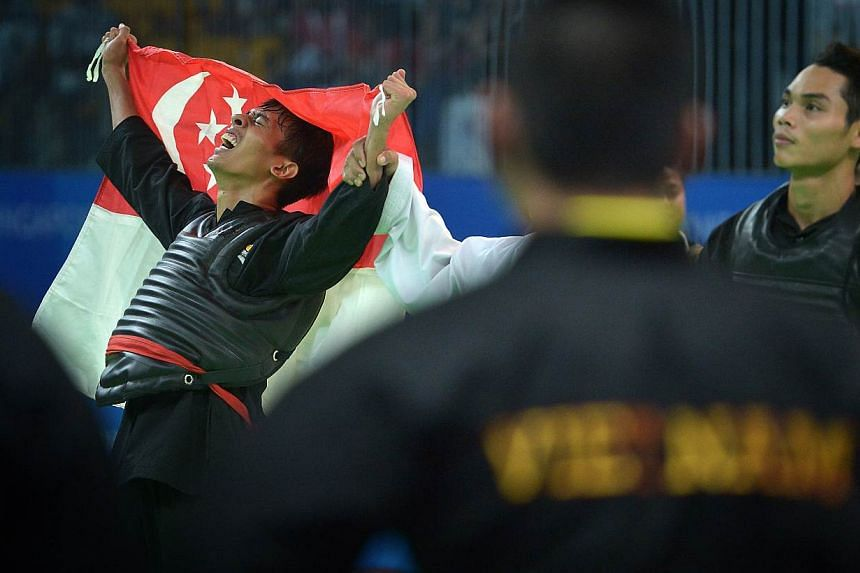 Singapore's silat exponent Nur Alfian celebrating after wininng the men's tanding Class F (70-75kg) final against Vietnamese world champion Tran Dinh Nam. It was the Republic's 80th gold medal of the SEA Games. -- ST PHOTO: KUA CH