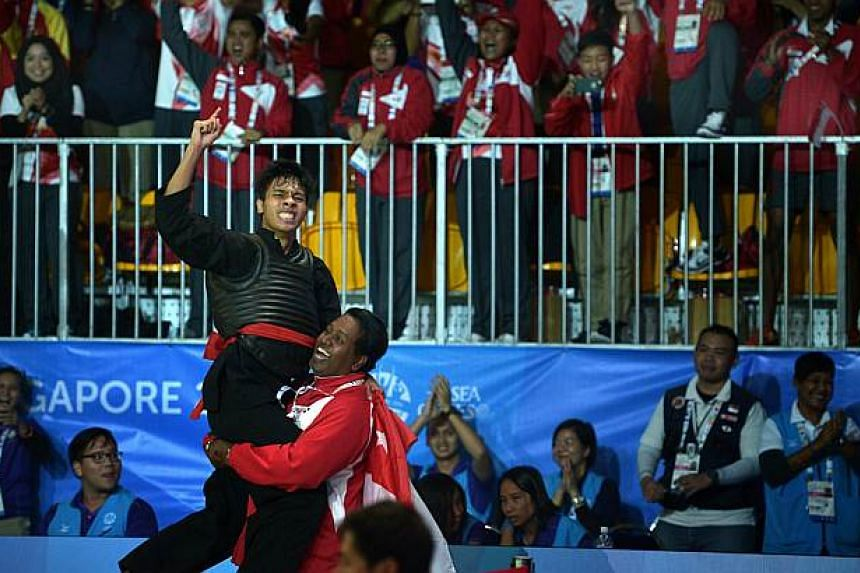Alfian leaping into the arms of Singapore Silat Federation head Sheik Alauddin to celebrate his win. -- ST PHOTO: KUA CHEE SIONG