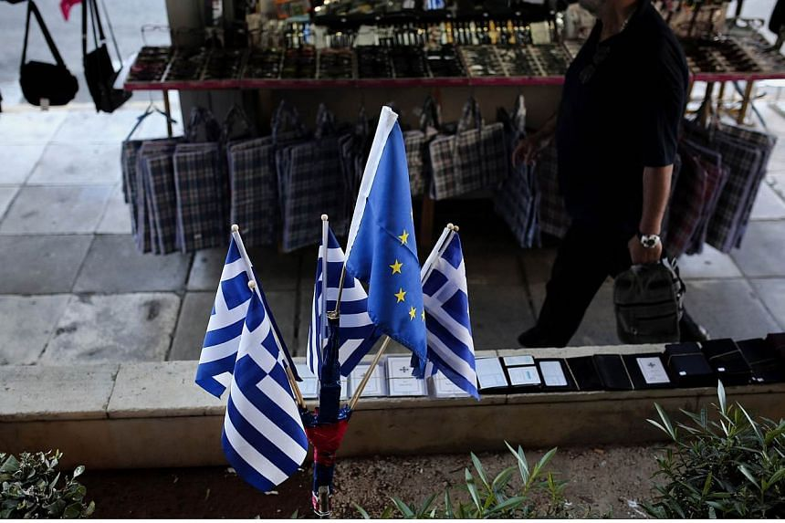 A man walks next to Greek national and European Union flags near the port of Piraeus on June 14, 2015. Greek and EU-IMF negotiators were locked in last-chance talks on Sunday to avert a default by Athens that could pave the way for a catastrophi