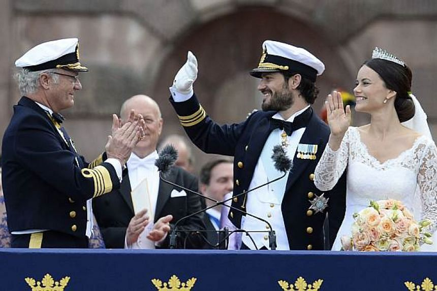 Sweden's King Carl XVI Gustaf (left) applauding the newly-wed couple Princess Sofia and Prince Carl Philip after their wedding ceremony at Stockholm Palace on June 13, 2015. -- PHOTO: AFP