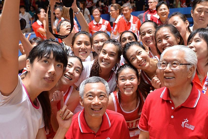 Singapore's victorious netballers taking a wefie with Prime Minister Lee Hsien Loong (centre) and President Tony Tan Keng Yam (right) after their 46-43 win over bitter rivals Malaysia in the final on June 7, 2015. -- PHOTO: THE NEW PAPER