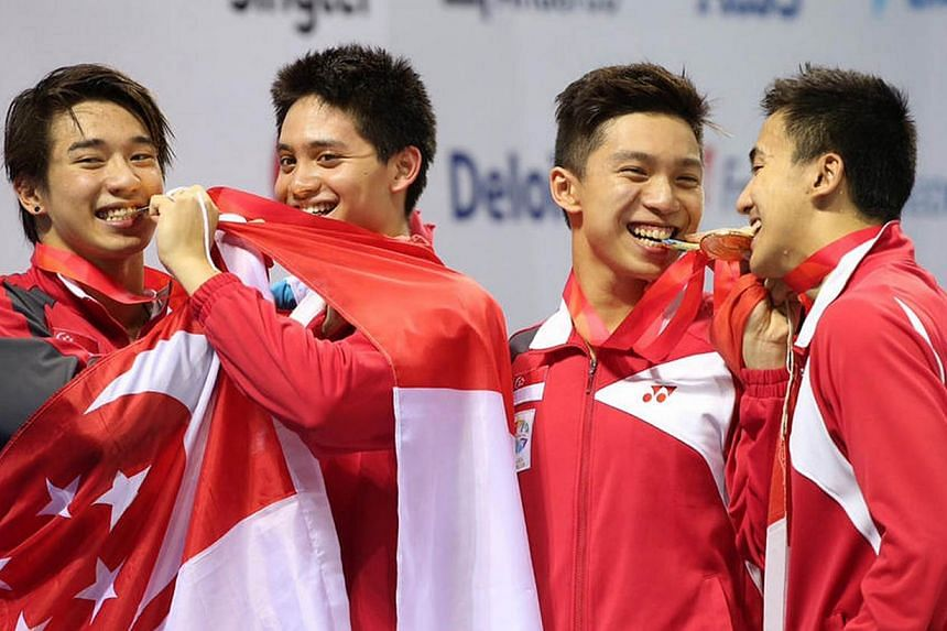 Swimmers (from left) Clement Lim, Joseph Schooling, Lionel Khoo and Quah Zheng Wen biting their gold medals after coming up tops in the 4x100m medley on June 11, 2015. Swimming contributed a record 23 golds to Singapore's medal tally, with Schooling
