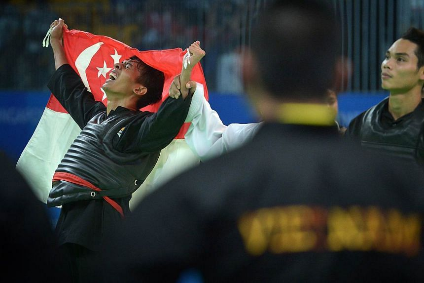 Silat exponent Nur Alfian, shedding tears of joy, celebrates with the Singapore flag after securing the Republic's 80th gold of the SEA Games. He beat Vietnamese world champion Tran Dinh Nam in the men's tanding Class F (70-75kg) final on June 1