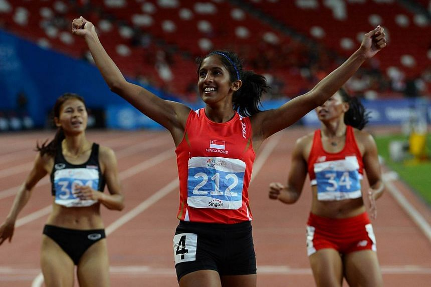 Shanti Pereira raising her arms in triumph after crossing the finishing line to win the women's 200m race in 23.60 seconds, a new national record, on June 10, 2015. It was Singapore's first gold in the event since Glory Barnabas' feat in 1973. -
