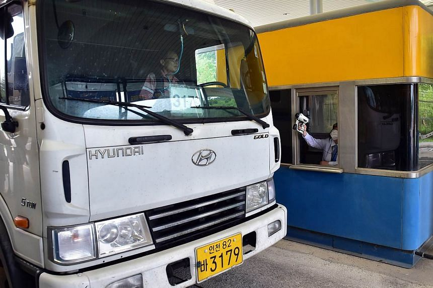 An official (right) checks the body heat of a South Korean truck driver arriving from North Korea's Kaesong Industrial Complex, at the South's CIQ (Customs, Immigration, Quarantine) gate at the inter-Korean transit office in Paju on June 13, 2015.&nb
