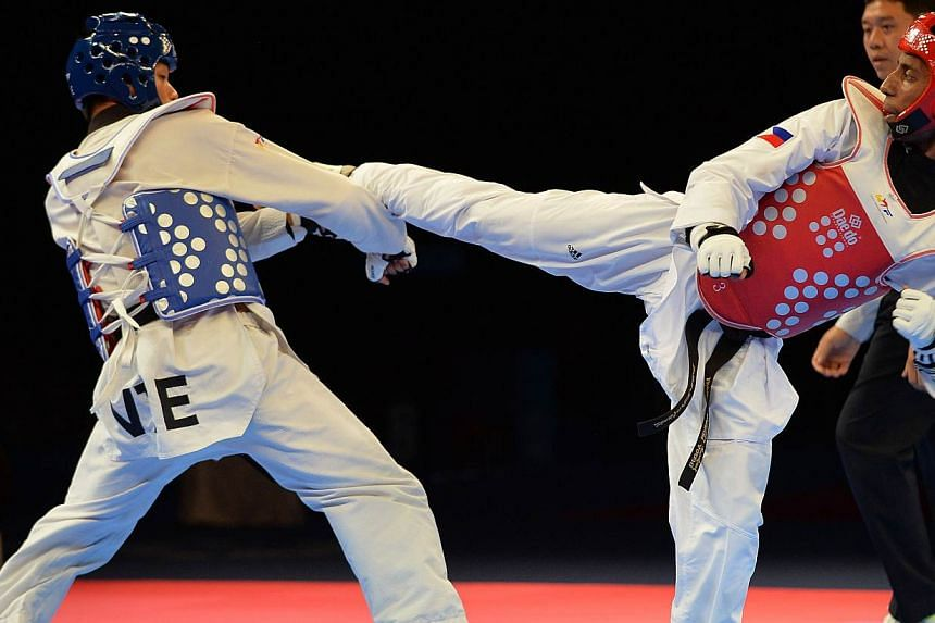 Trung Duc Phan of Vietnam (left) competes against Samuel Morrison of the Philippines (right) during the men's under 68kg taekwondo final at the 28th Southeast Asian Games (SEA Games) in Singapore on June 14, 2015.The Philippines' won two of the