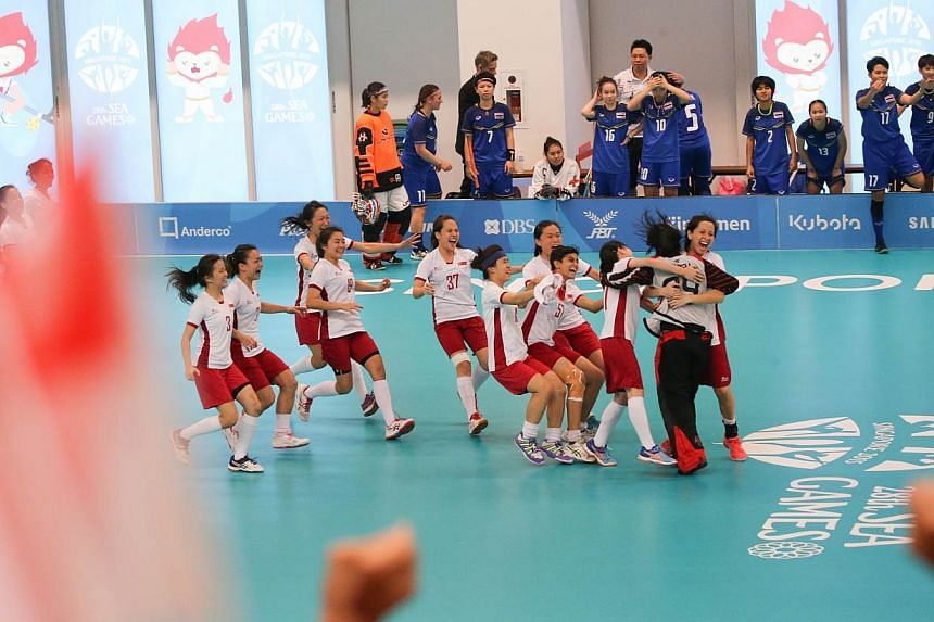 The Singapore floorball women's team celebrating after defeating Thailand in the SEA Games floorball finals. Singapore won 2-1 on penalties after the game ended 3-3. -- ST PHOTO: ONG WEE JIN