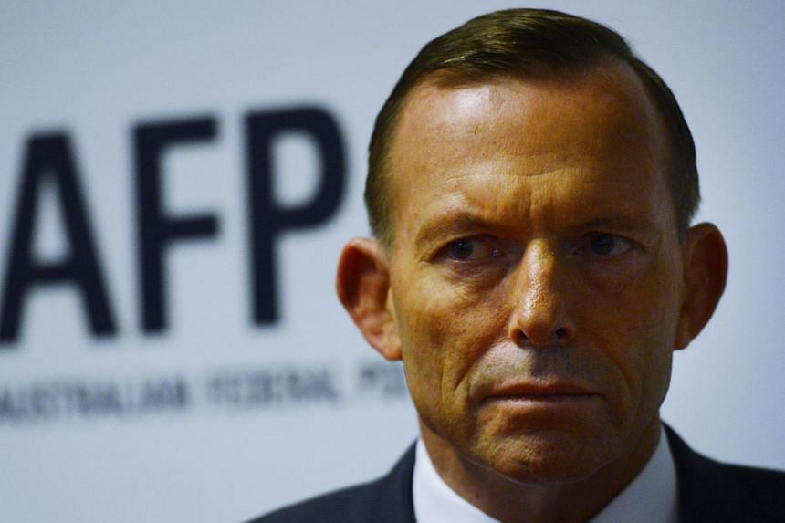 Australian Prime minister Tony Abbott looks on as he visits the Endeavour Hills police station in Melbourne, Australia, on June 12, 2015. Australian Prime Minister Tony Abbott did not deny the June 11, 2015 allegations that border officials paid peop
