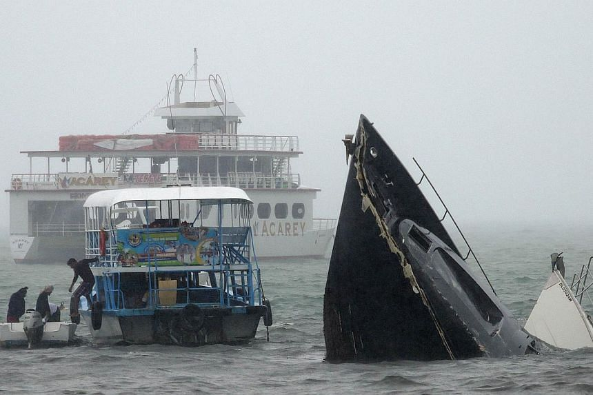 A man gets off a ferry next to two sunken yachts after hurricane Carlos in Acapulco, Guerrero State, Mexico on June 14, 2015. Hurricane Carlos was downgraded to a tropical storm Sunday off Mexico's Pacific coast, forecasters said. -- PHOTO: AFP
