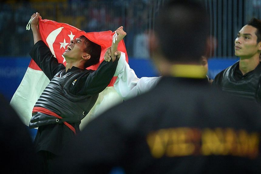 Local silat exponent Muhammad Nur Alfian Juma'en celebrating his victory against Vietnam's world champion Tran Dinh Nam yesterday. Refusing to quit despite a bleeding foot, the 18-year-old clinched Singapore's 80th gold at the SEA Games. The Republic