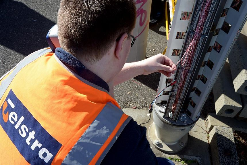 A Telstra field technician conducting maintenance work on one of the company's communication pillars in Melbourne, Australia, on Thursday, Aug 16, 2012. -- PHOTO: BLOOMBERG