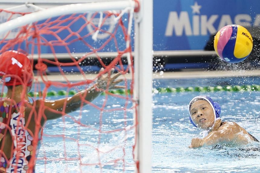 Singapore's Loke En Yuan (right) scores a goal against Indonesia in the women's water polo round robin match 1 during the 28th SEA Games at the OCBC Aquatics Centre on June 10, 2015. -- ST PHOTO: KEVIN LIM