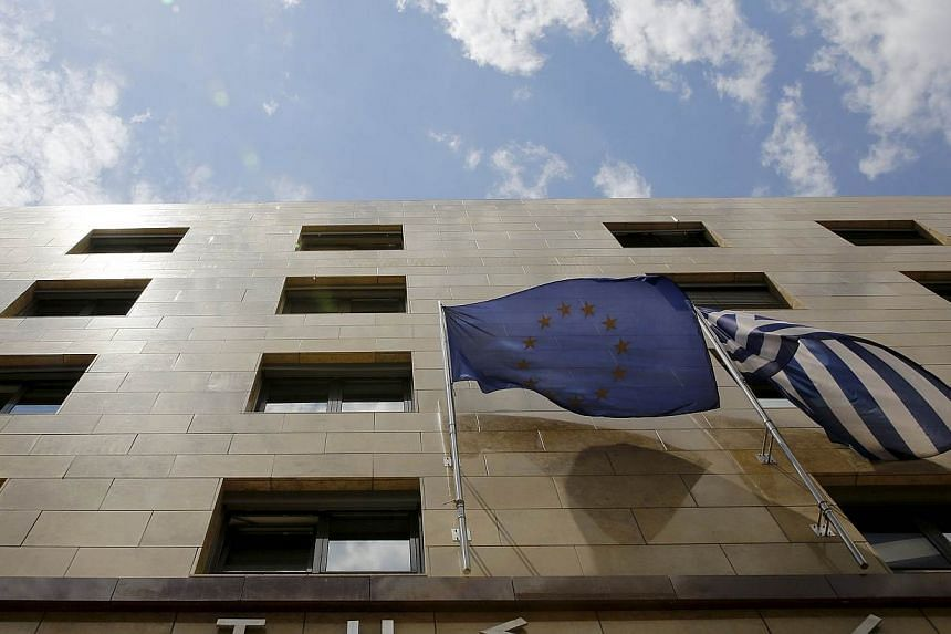A European Union flag (left) and a Greek national flag flutter at the entrance of the Bank of Greece headquarters in Athens on June 11, 2015. The collapse of talks between Greek ministers and their bailout creditors and a slide in Wall Street le