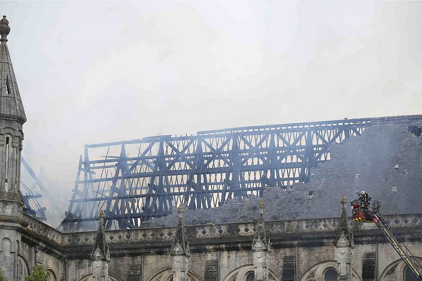 French firefighters try to extinguish the fire that damaged the roof of the Saint-Donatien Basilica in Nantes, western France on June 15, 2015. -- PHOTO: REUTERS