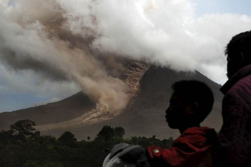 Residents sit on their motorcycle as they watch an eruption at Mount Sinabung, in Namanteran village in Karo Regency, Indonesia's North Sumatra province on June 14, 2015. -- PHOTO: REUTERS