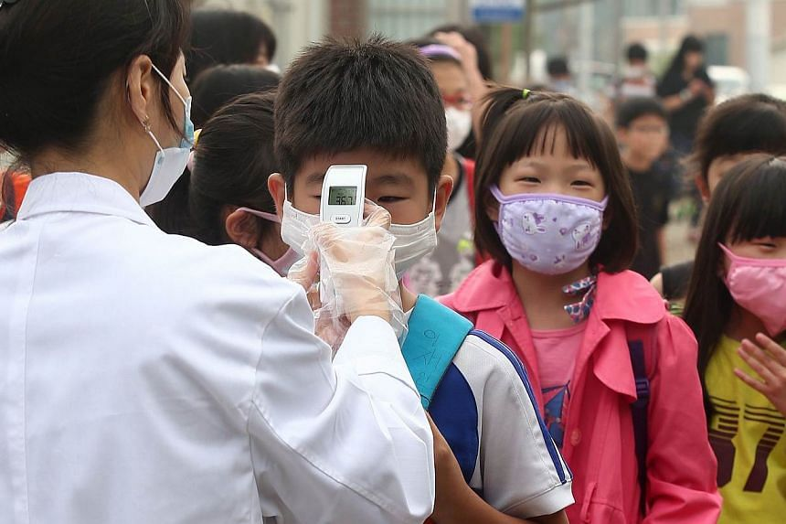A health worker checks the body heat of children wearing face masks at an elementary school in Pyeongtaek, 65km south of Seoul, on June 15, 2015 as the school is reopened after a temporary closure in response to public fears over Middle East Respirat