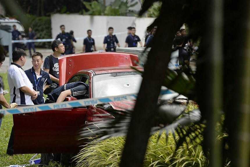 Singapore police officers inspect a red sedan car with a bullet hole on the windscreen which was involved in an early morning shooting incident after it illegally bypassed a police vehicular checkpoint, on May 31, 2015.One of the passengers in