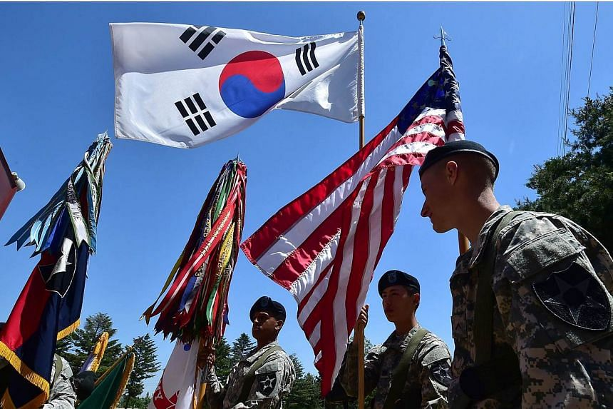 US soldiers hold the flags of South Korea (top) and the US (right) before a South Korea-US Combined Division activation ceremony at a US Army base in Uijeongbu, north of Seoul, on June 3, 2015. North Korea said on Monday, June 15, that it is rea