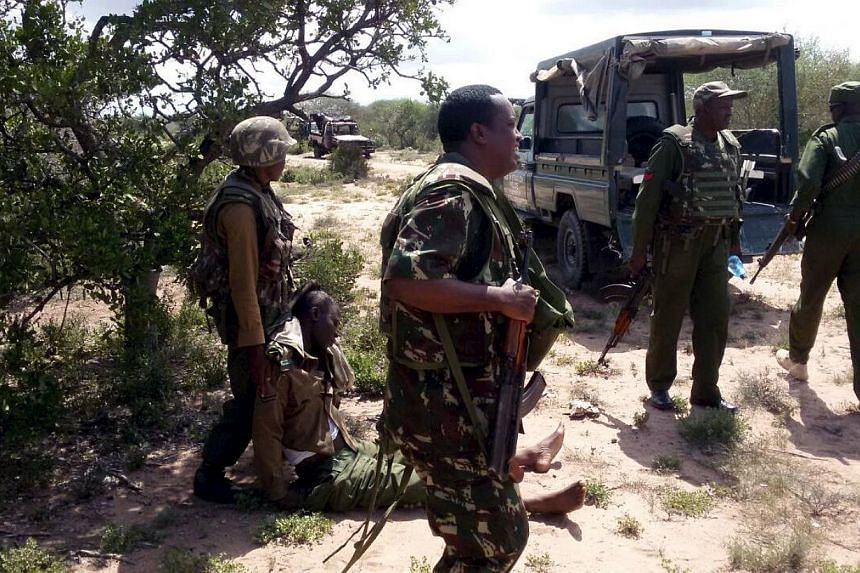 An injured administration police officer is helped by his colleagues after they were ambushed by Somalia's Al-Shebab fighters in Yumbis village near the Kenya-Somalia border on May 26, 2015.A British militant fighting for Somalia's Al-Qaeda aff