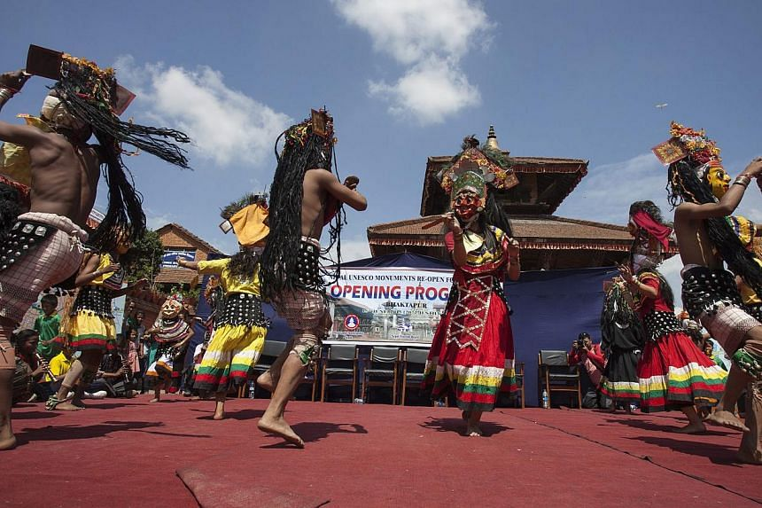 Local artists perform a ritual dance during the opening of Bhaktapur to tourists at Darabar Square, Bhaktapur, Nepal, on June 15, 2015.Nepal reopened hundreds of earthquake-damaged monuments at heritage sites on Monday,trying to draw visi