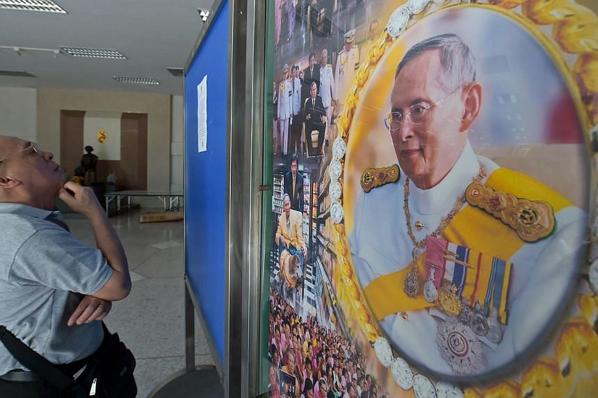 A Thai well-wisher reads a statment from the royal bureau next to a portrait of Thai King Bhumibol at Siriraj hospital in Bangkok on June 1, 2015. Thailand's junta has banned a journalists' association from holding a debate on controversial lese maje