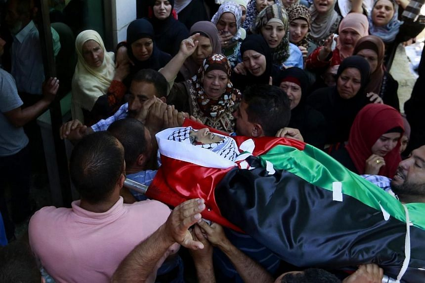 Palestinians carry the body of 21-year-old Abdallah Ghanayem, during his funeral in the west bank village of Qafr Malik near the West Bank city of Ramallah on Sunday. According to Palestinian medical sources, Israeli soldiers killed Ghanayem by hitti