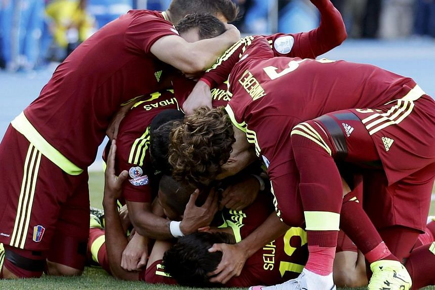 Venezuela players mob teammate Jose Rondon (obscured) as they celebrate his goal against Colombia during their first round Copa America 2015 soccer match at Estadio El Teniente in Rancagua, Chile on Sunday. -- PHOTO: REUTERS