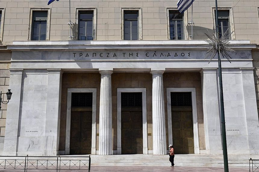 A woman walking past Bank of Greece headquarters in central Athens on June 15, 2015. US stocks retreated, with the Standard & Poor's 500 Index slipping below its average price during the past 100 days, after weekend negotiations between Greece an