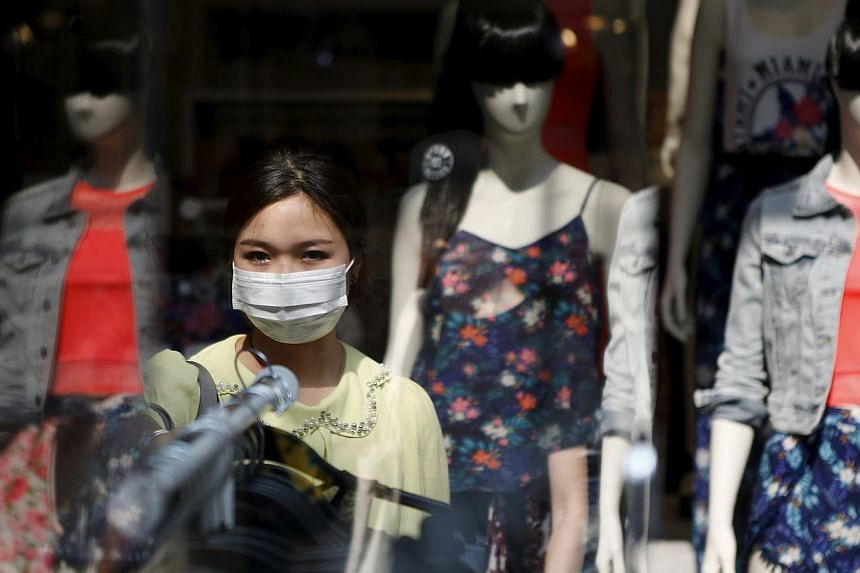 A woman wearing a mask to prevent contracting Middle East Respiratory Syndrome (MERS) shops at a clothing store in central Seoul, South Korea, on June 15, 2015. -- PHOTO: REUTERS